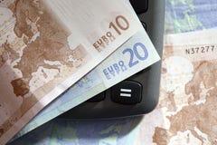 Nota del euro diez y veinte sobre una calculadora Imágenes de archivo libres de regalías