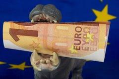 Nota del euro 10 en boca de una estatuilla del hipopótamo Imágenes de archivo libres de regalías