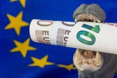 Nota del euro 10 en boca de una estatuilla del hipopótamo Imagenes de archivo