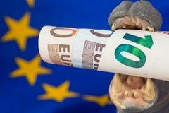 Nota del euro 10 en boca de una estatuilla del hipopótamo Foto de archivo