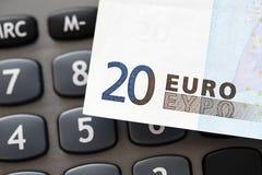 Nota del euro veinte sobre una calculadora Imagen de archivo