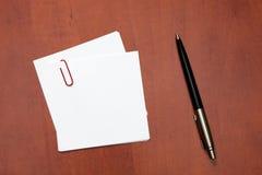 Nota del Libro Blanco con un clip y una pluma Imagen de archivo libre de regalías