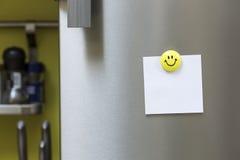 Nota del papel en blanco con la ejecución del imán en puerta del refrigerador Imágenes de archivo libres de regalías