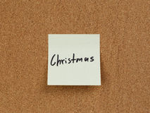Nota del recordatorio de la Navidad sobre tablero del corcho Imágenes de archivo libres de regalías