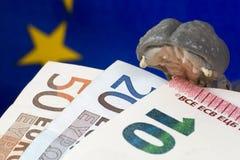 Nota dell'euro 10 in bocca di una figurina dell'ippopotamo Immagini Stock
