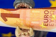 Nota dell'euro 10 in bocca di una figurina dell'ippopotamo Immagini Stock Libere da Diritti