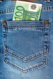 nota dell'euro 100 in una tasca delle blue jeans Fotografia Stock Libera da Diritti