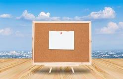 Nota della carta in bianco sul bordo del sughero con il fondo del cielo blu Fotografia Stock Libera da Diritti