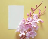 Nota della carta con i fiori rosa dell'orchidea fotografia stock