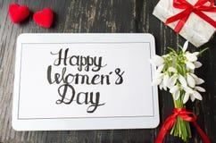 Nota di calligrafia del giorno delle donne felici su una compressa fotografia stock libera da diritti
