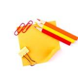 Nota di carta appiccicosa arancio con le clip e le matite rosse Fotografia Stock Libera da Diritti