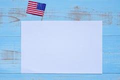 Nota di carta in bianco con la bandiera degli Stati Uniti d'America su fondo di legno blu Festa dei veterani, memoriale di U.S.A. immagine stock