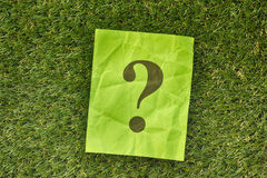 Nota di carta con il punto interrogativo su erba verde fotografie stock libere da diritti