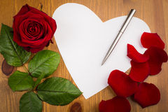 Nota di carta del cuore con Rose Pettles And Pen su legno Immagini Stock Libere da Diritti