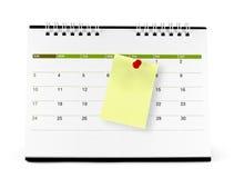 Nota di carta gialla con la puntina da disegno rossa alla pagina del calendario Fotografie Stock