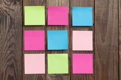 Nota di carta multicolore degli autoadesivi su di legno Fotografia Stock