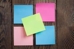 Nota di carta multicolore degli autoadesivi su di legno Fotografie Stock