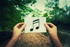 Nota di musica della tenuta fotografia stock