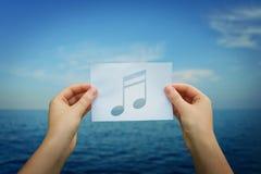 Nota di musica della tenuta fotografie stock