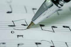 Nota di musica di scrittura della mano con la penna a sfera fotografia stock