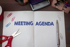 Nota di scrittura che mostra ordine del giorno di riunione Foto di affari che montra gli oggetti che i partecipanti sperano di co fotografia stock libera da diritti