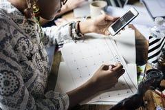 Nota di scrittura di pianificazione della donna sul calendario immagini stock libere da diritti