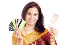 Nota di valuta della holding della donna e carta di credito indiane Fotografie Stock