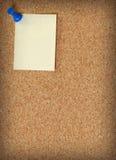 Nota die aan corkboard wordt vastgespijkerd Stock Fotografie