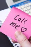 A nota do amor no escritório diz CHAMA-ME Imagem de Stock Royalty Free