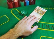 Nota do Euro 50 que está sendo trocada por microplaquetas de jogo em uma tabela verde do vinte-e-um de feltro no casino Foto de Stock Royalty Free