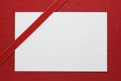 Nota en blanco blanca con la cinta roja Fotografía de archivo libre de regalías