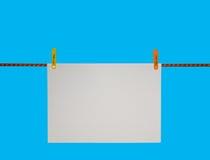 Nota en blanco sobre una cuerda para tender la ropa Fotografía de archivo libre de regalías