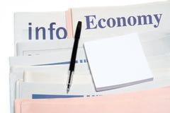 Nota en pen, over gestapelde economiekranten Stock Fotografie