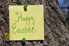 Nota feliz amarilla del papel de pascua fijada en un árbol Imágenes de archivo libres de regalías