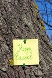 Nota feliz amarilla del papel de pascua fijada en un árbol Imagenes de archivo