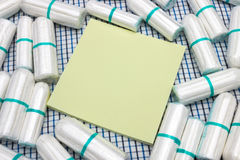 Nota gialla del bastone e tamponi puliti sanitari del cotone di mestruazione sul copriletto del plaid Protezione di igiene della  Immagine Stock Libera da Diritti