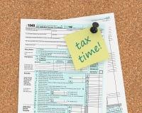 Nota met de tekst van de belastingstijd en 1040 belastingsvorm Stock Foto