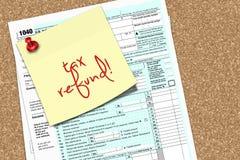 Nota met de tekst van de belastingsterugbetaling en vorm 1040 aan speldraad die wordt gespeld Stock Foto