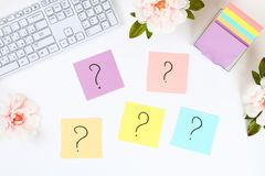 Nota multicolora de las etiquetas engomadas con el signo de interrogación en la mesa blanca al lado de una taza de café y de tecl fotografía de archivo libre de regalías