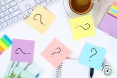 Nota multicolore degli autoadesivi con il punto interrogativo sul desktop bianco accanto ad una tazza di caffè e della tastiera fotografia stock
