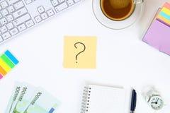 Nota multicolore degli autoadesivi con il punto interrogativo sul desktop bianco accanto ad una tazza di caffè e della tastiera fotografia stock libera da diritti