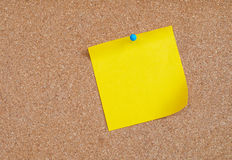 Nota pegajosa amarela na placa da cortiça imagem de stock royalty free