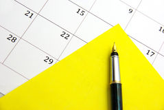 Nota pegajosa amarela no calendário Fotos de Stock
