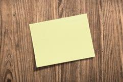 Nota pegajosa amarilla sobre tarjeta de madera. Fotos de archivo libres de regalías