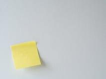 Nota pegajosa amarilla sobre una pared blanca Fotos de archivo