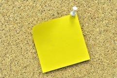 Nota pegajosa amarilla sobre una tarjeta del corcho. Foto de archivo libre de regalías