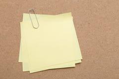 Nota pegajosa amarilla y clip de papel Fotos de archivo libres de regalías