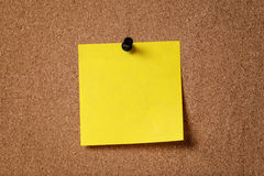 Nota pegajosa del recordatorio amarillo sobre tablero del corcho Imágenes de archivo libres de regalías