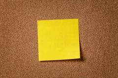 Nota pegajosa del recordatorio amarillo sobre tablero del corcho Foto de archivo