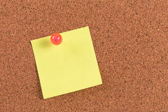 Nota pegajosa del recordatorio amarillo sobre tablero del corcho Imagen de archivo libre de regalías